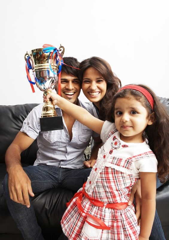 kid raising a trophy with happy parents